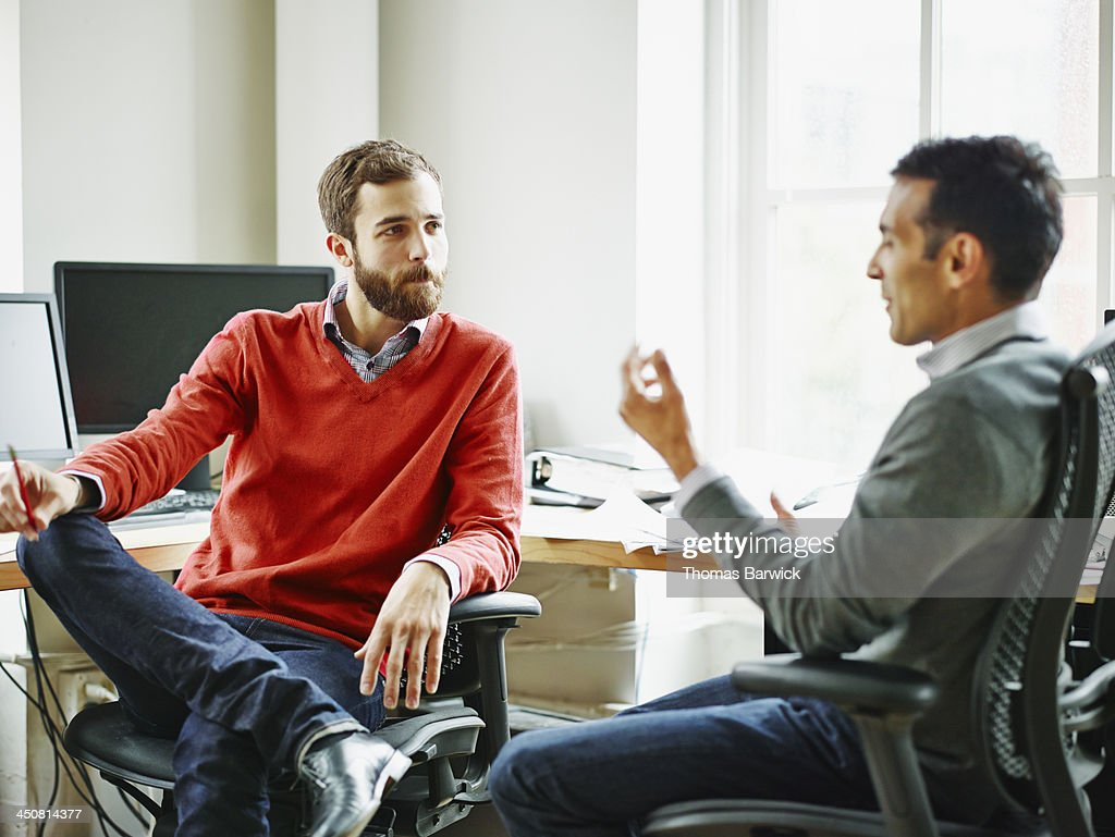 Businessmen in discussion in office workstation