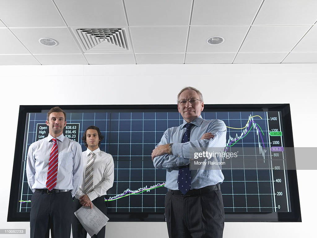 Businessmen in front of graphs on screen : Stock Photo