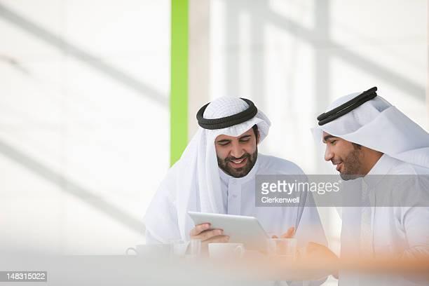 Businessmen in kaffiyehs using digital tablet