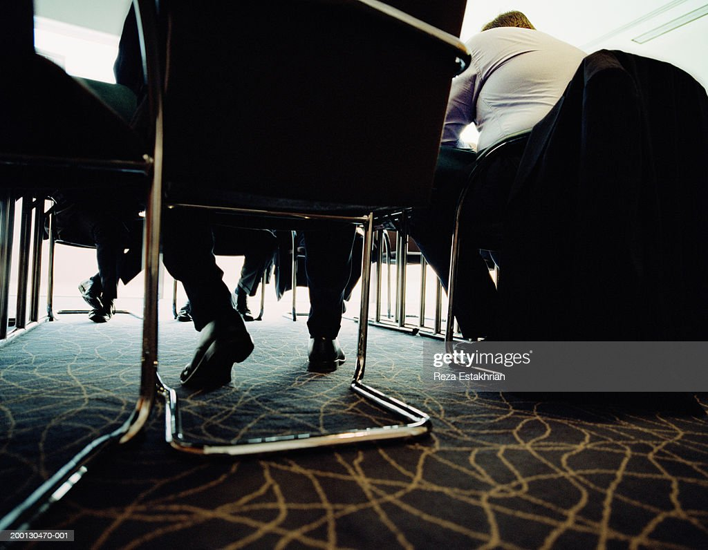 Businessmen in meeting, low angle view (focus on legs under table) : Stock Photo