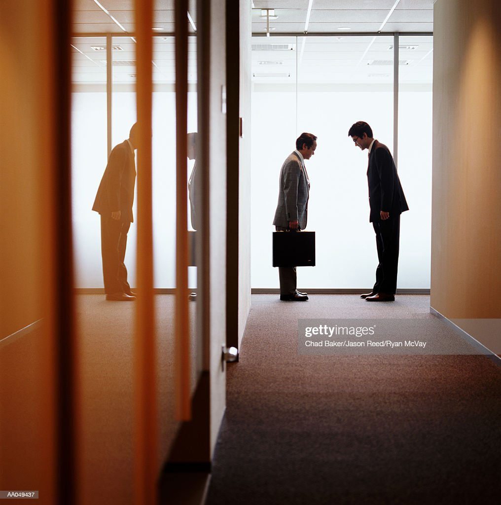 Businessmen in office hallway bowing to each other, side view