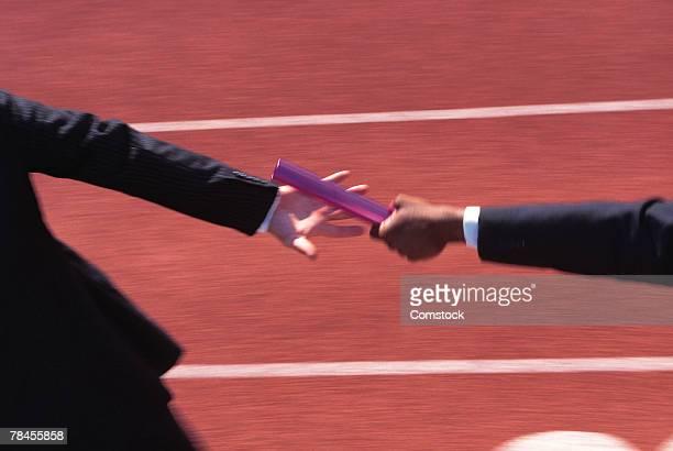 Businessmen in relay race passing baton