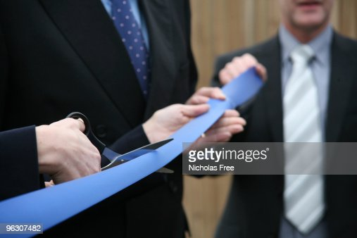Businessmen in suits holding scissors cutting a blue ribbon