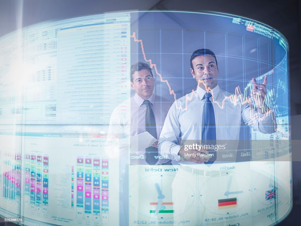 Businessmen inspecting graph on interactive display