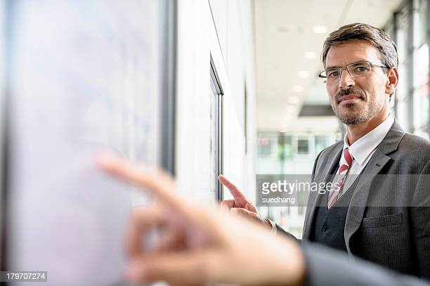 Businessmen interacting with touch screens