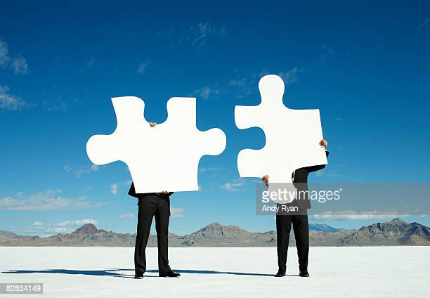 Businessmen Joining Giant Puzzle Pieces in Desert.