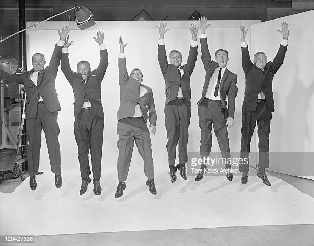 Businessmen jumping mid air with raised arms, smiling
