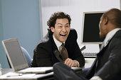 Businessmen laughing at work
