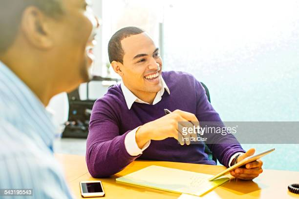 Businessmen laughing in office meeting