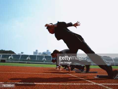 Businessmen leaving starting block : Stock Photo