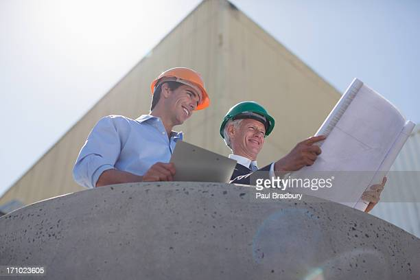 Businessmen looking at blueprints and using cell phone outdoors