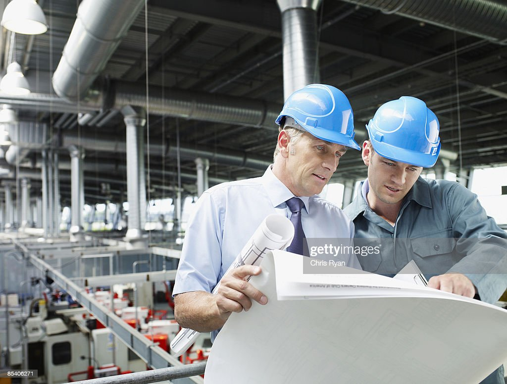 Businessmen looking at blueprints in factory : Stock Photo