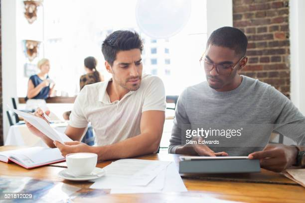 Businessmen looking at digital tablet in meeting