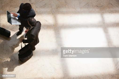 Businessmen looking at laptop in lobby : Stock Photo