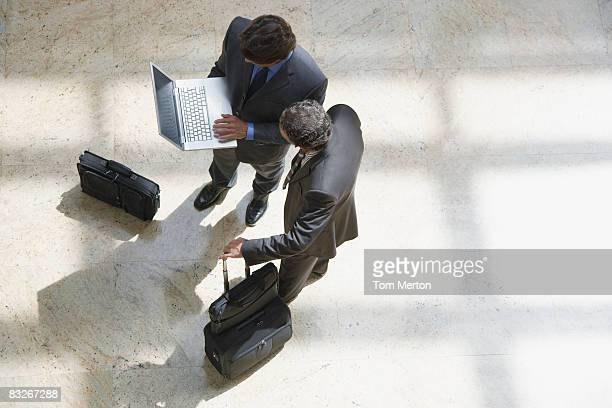 Businessmen looking at laptop in lobby