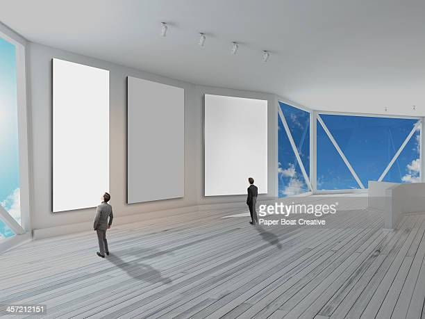 businessmen looking at large white blank canvas