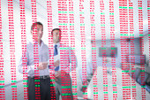 Businessmen looking at red and green figures seen through screen