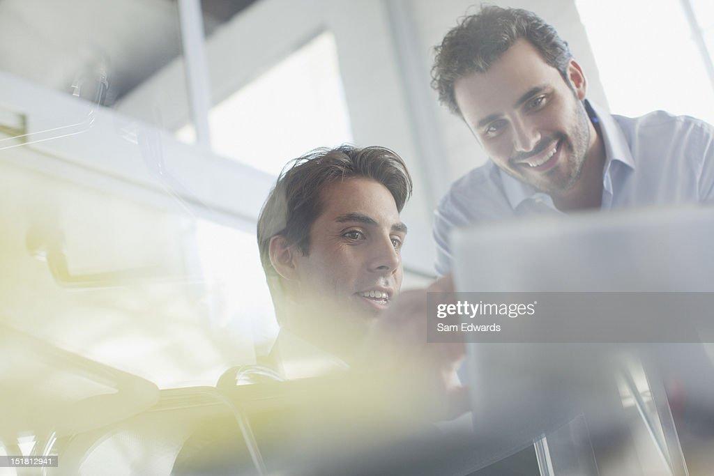 Businessmen looking down at paperwork : Stock Photo