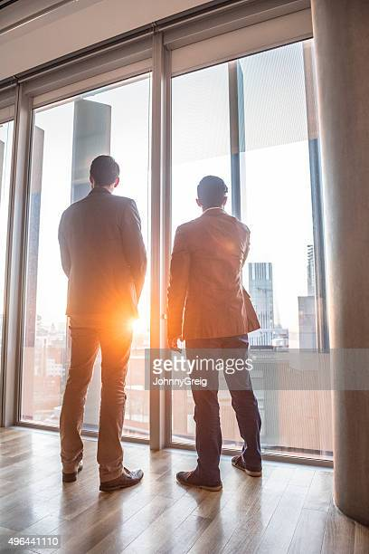 Businessmen looking out of modern office window