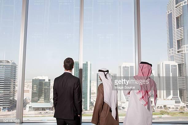 Businessmen looking through window in dubai office