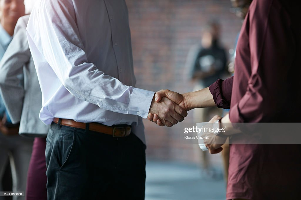 Businessmen making handshake at conference : Stock Photo