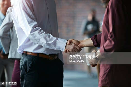 Businessmen making handshake at conference : Stock Photo