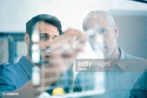 Businessmen making plan on glass wall in office