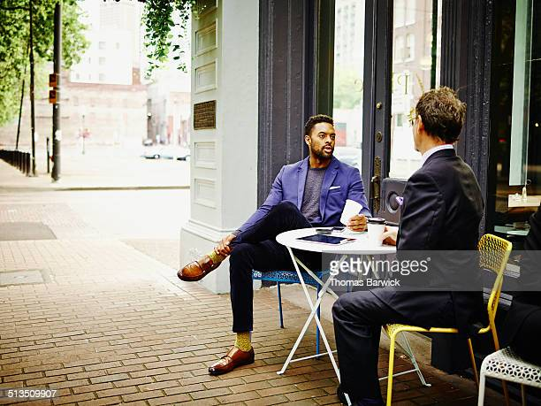Businessmen meeting at outdoor table of urban cafe