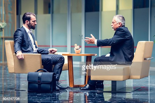 Businessmen negotiating in a modern office lobby