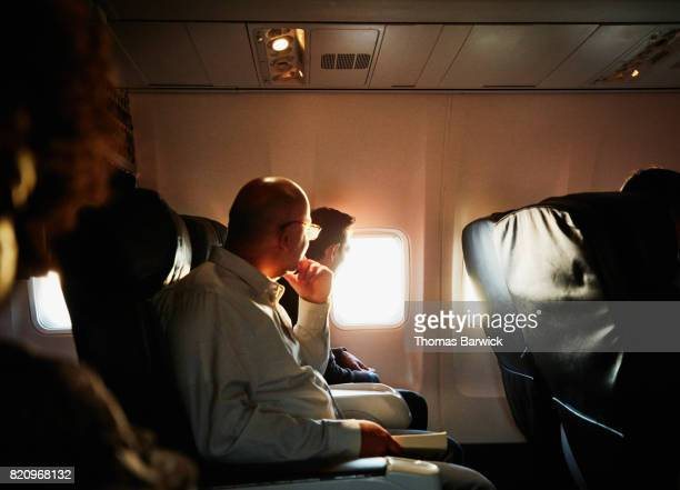 Businessmen on flight watching sunset out of airplane window