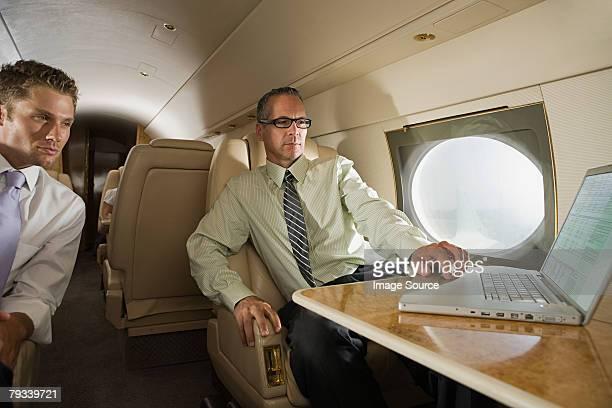 Hommes d'affaires avec ordinateur portable sur le jet