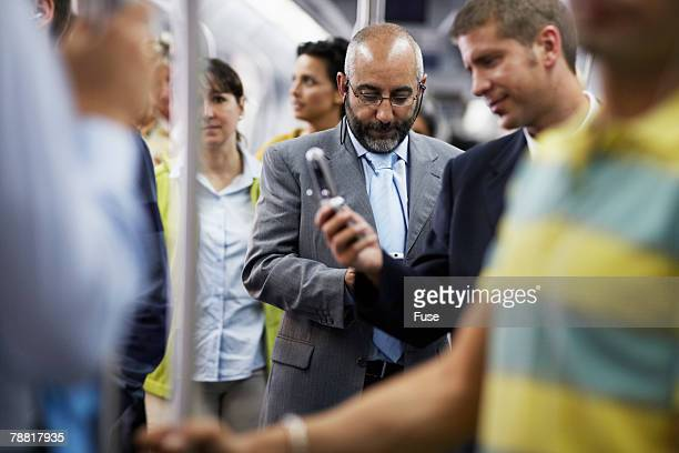 Businessmen on Subway Looking at Cell Phones