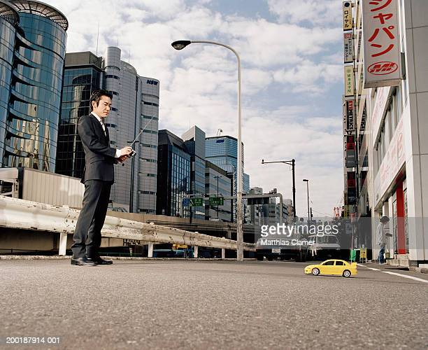 Businessmen operating remote controlled toy car, side view