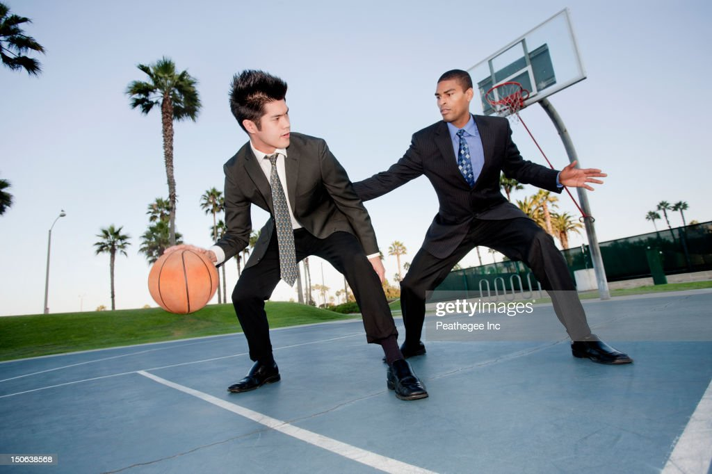 Businessmen playing basketball outdoors : Stock Photo