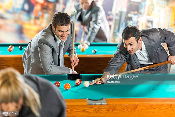 Businessmen playing billiard after work.