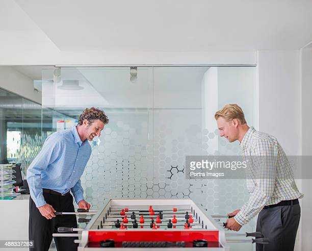 Businessmen playing foosball in office