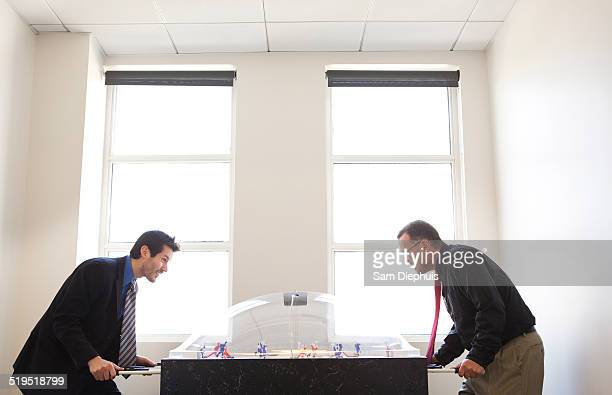 Businessmen playing foosball together in office