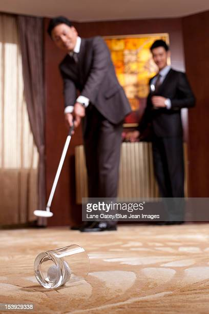Businessmen playing golf in a luxurious room
