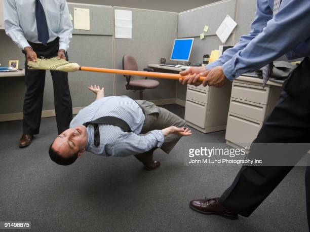 Businessmen playing limbo with broom in office