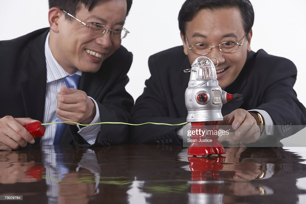 Businessmen playing with toy robot : Stock Photo
