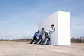 Businessmen pushing wall outdoors
