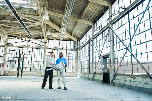 Businessmen reading blueprints in empty warehouse