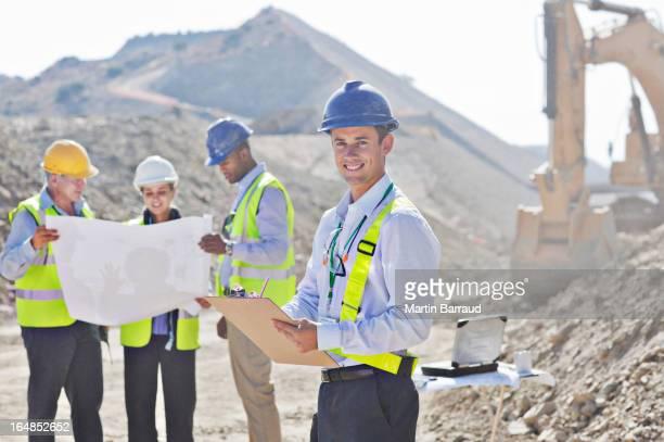 Businessmen reading blueprints in quarry