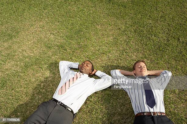 Businessmen relaxing on the grass