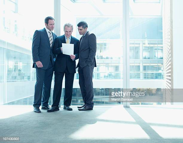 Businessmen reviewing paperwork near glass wall in office