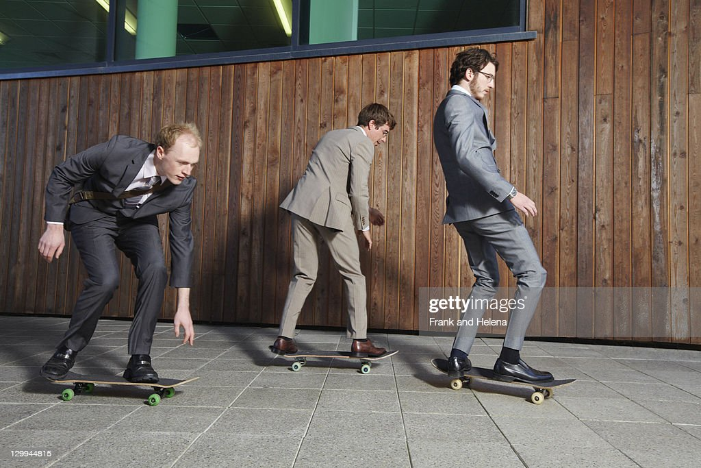 Businessmen riding skateboards : Stock Photo
