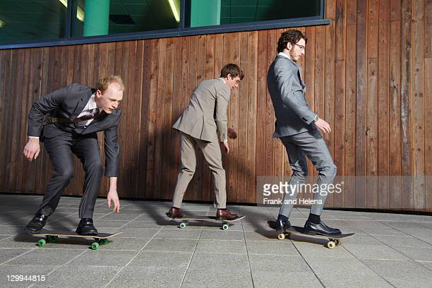 Businessmen riding skateboards