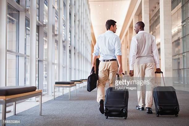 Businessmen rolling luggage in hallway