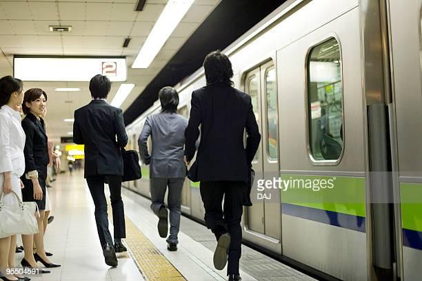 Businessmen running in the platform