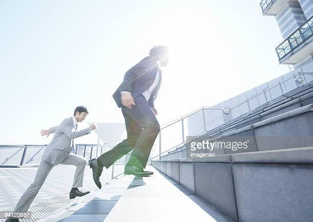 Businessmen running up stairs